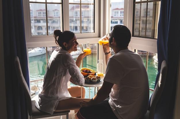 Giovani coppie felici che godono della prima colazione sulla terrazza
