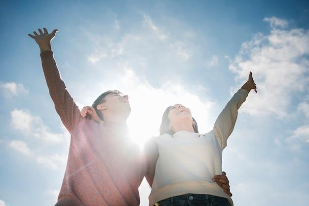 Giovani coppie felici che guardano in cielo