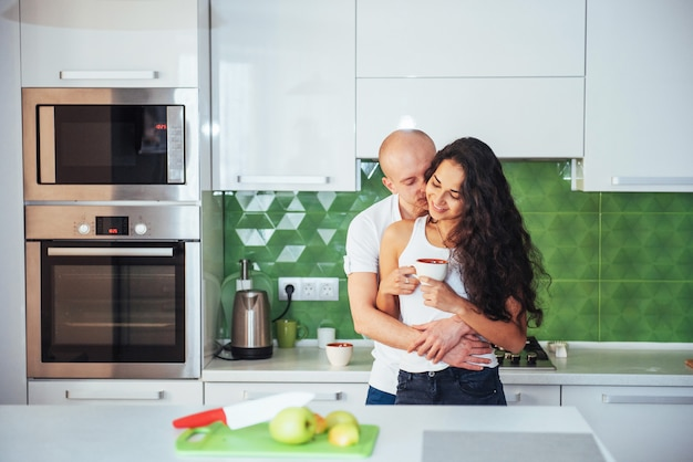 Giovani coppie felici che mangiano caffè nella cucina