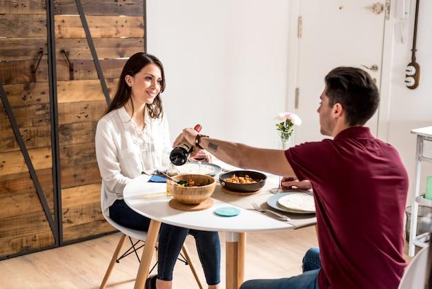 Giovani coppie felici che mangiano e che bevono vino a casa
