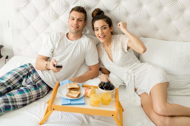 Giovani coppie felici che mangiano prima colazione nella stanza di lusso