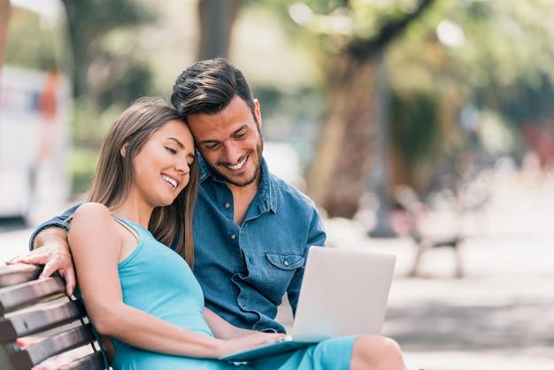 Giovani coppie felici che per mezzo del computer portatile che si siede su un banco in città all'aperto