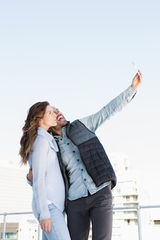 Giovani coppie felici che prendono selfie sul telefono cellulare all'aperto