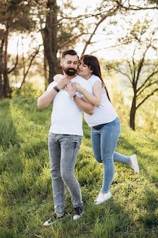 Giovani coppie felici che prevedono bambino nel parco di estate