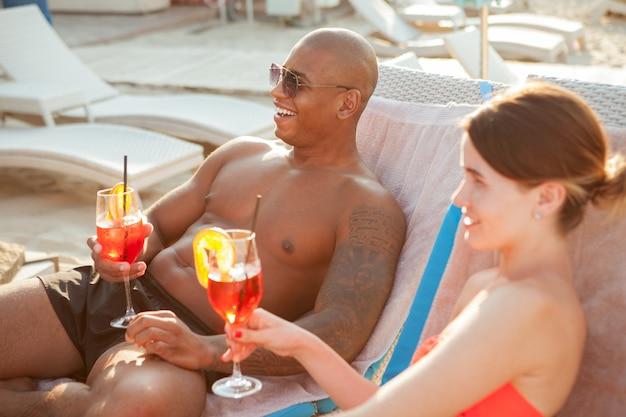 Giovani coppie felici che ridono, avendo cocktail sulla spiaggia al lussuoso centro balneare. uomo africano bello che si distende sulla spiaggia con la sua ragazza