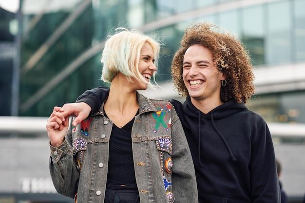 Giovani coppie felici che ridono nel fondo urbano