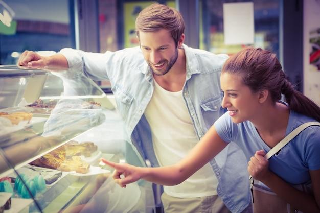Giovani coppie felici che scelgono torta
