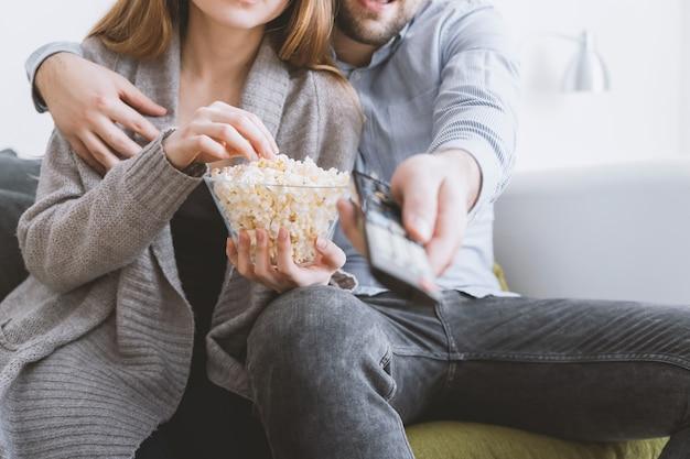Giovani coppie felici che si rilassano e che guardano tv a casa