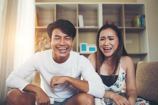 Giovani coppie felici che si rilassano e che guardano tv al salone