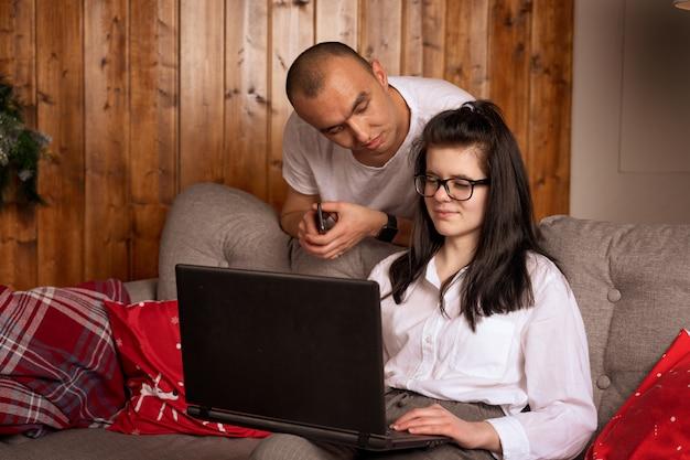 Giovani coppie felici che si siedono insieme guardando un computer portatile