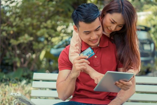 Giovani coppie felici che si siedono nel giardino e che tengono una compressa e una carta di credito e che attualmente acquistano i prodotti