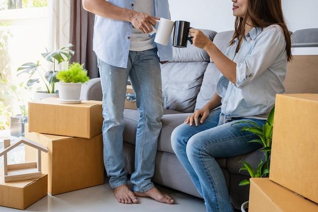 Giovani coppie felici che si spostano nella nuova casa seduta e rilassante sul divano