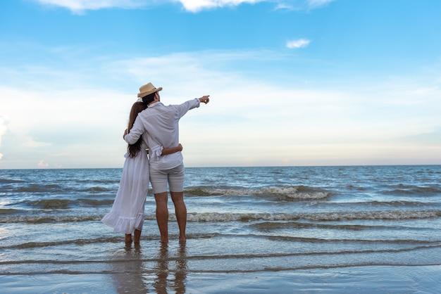 Giovani coppie felici che si tengono e che ridono con godendo insieme sulla spiaggia di estate.