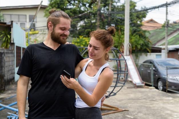 Giovani coppie felici che sorridono mentre usando insieme telefono cellulare nelle vie all'aperto
