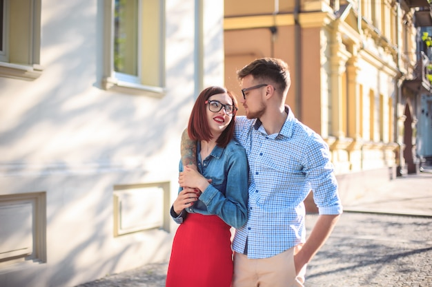 Giovani coppie felici che stanno alla via della città e che ridono il giorno soleggiato luminoso