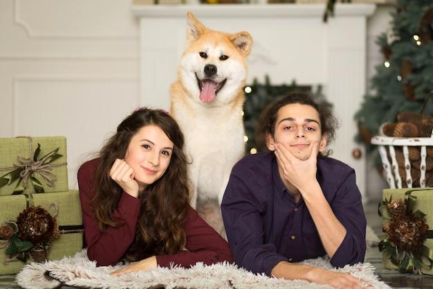 Giovani coppie felici che stringono a sé il cane adorabile di inu di akita con sul pavimento per le feste di natale a casa.