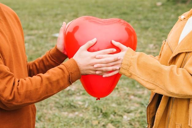Giovani coppie felici che tengono pallone a forma di cuore
