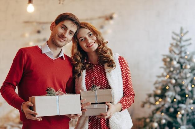 Giovani coppie felici con i regali di natale