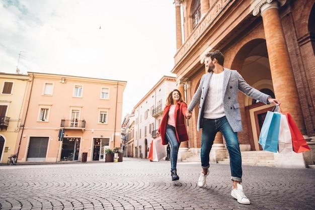 Giovani coppie felici con i sacchetti della spesa che corrono nella città