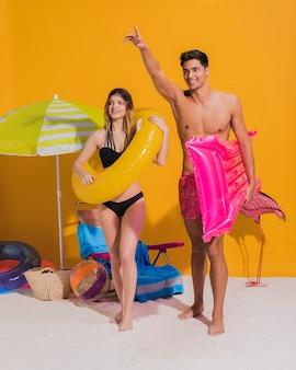 Giovani coppie felici con il cerchio di nuoto e materasso sulla spiaggia