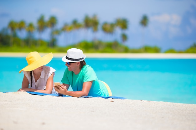 Giovani coppie felici con il telefono cellulare sulla spiaggia