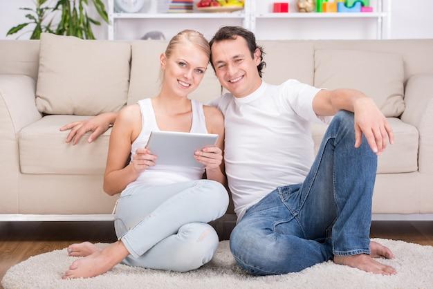 Giovani coppie felici con la compressa a casa.