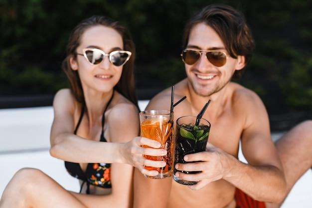 Giovani coppie felici con le bevande che si rilassano sulla spiaggia