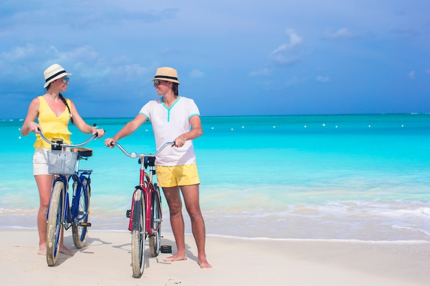 Giovani coppie felici con le bici sulla vacanza della spiaggia di estate