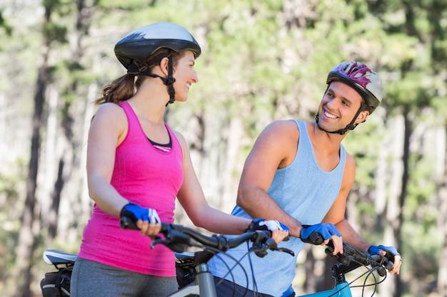 Giovani coppie felici con le biciclette alla foresta