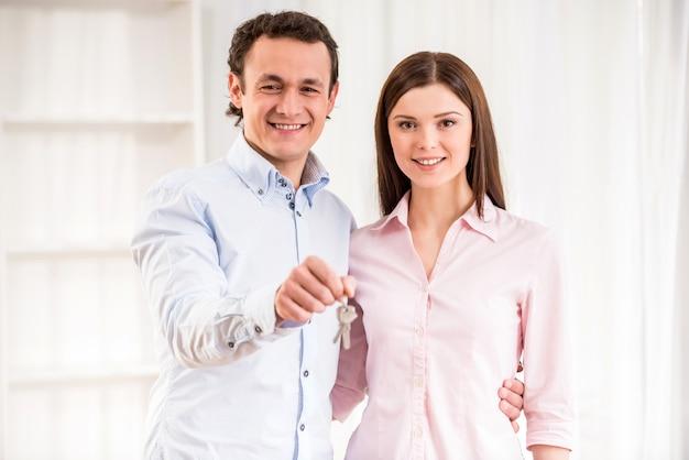 Giovani coppie felici con le chiavi nel loro nuovo appartamento.