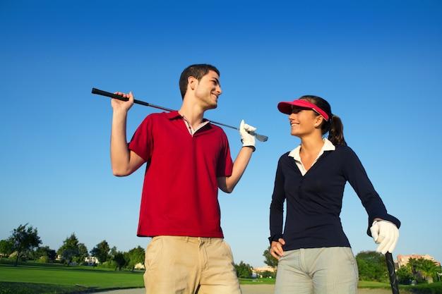 Giovani coppie felici dei giocatori delle coppie del campo da golf che parlano