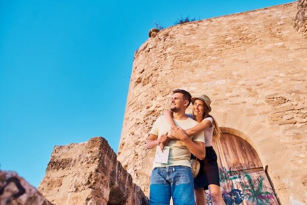 Giovani coppie felici dei viaggiatori che guardano tramonto