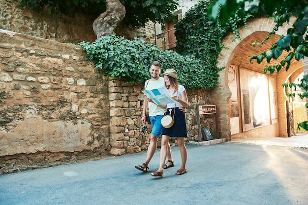 Giovani coppie felici dei viaggiatori che tengono mappa in mani