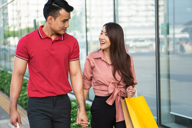 Giovani coppie felici di clienti che camminano nella strada dei negozi verso e che tengono i sacchetti della spesa variopinti