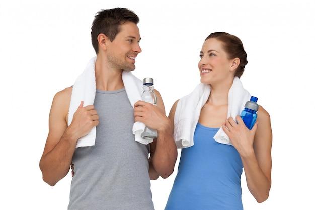 Giovani coppie felici di misura con le bottiglie di acqua