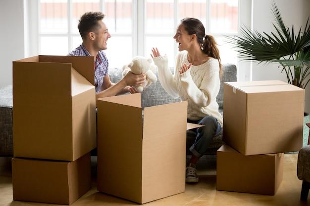 Giovani coppie felici divertendosi scatole di imballaggio nella nuova casa