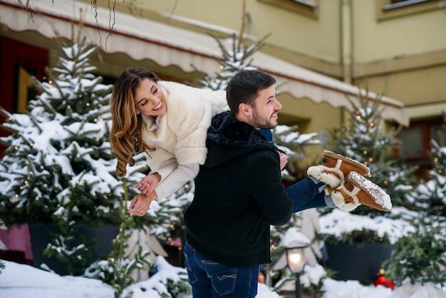 Giovani coppie felici divertendosi sul paesaggio urbano di inverno dell'albero di natale con le luci. vacanze invernali, natale e capodanno.
