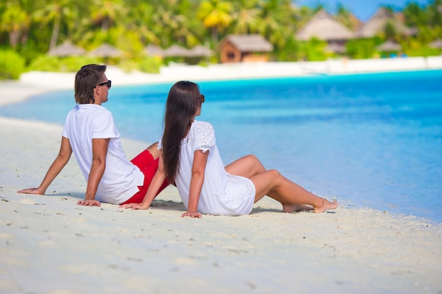 Giovani coppie felici durante la vacanza tropicale della spiaggia