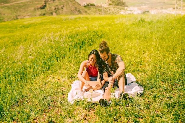 Giovani coppie felici facendo uso della compressa nella radura