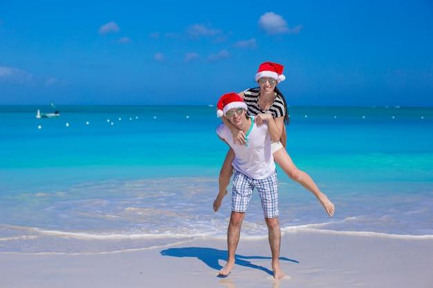 Giovani coppie felici in cappelli rossi di santa durante la loro vacanza tropicale