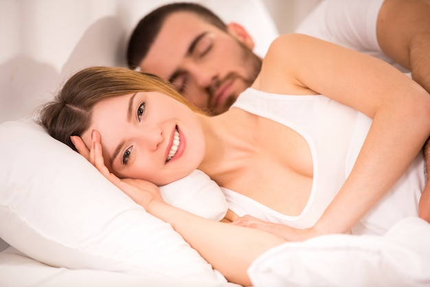Giovani coppie felici in letto bianco a casa.
