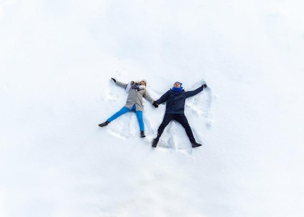 Giovani coppie felici nel parco di inverno che si trova sulla neve. making snow angel