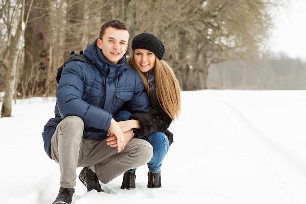 Giovani coppie felici nel parco di inverno divertendosi