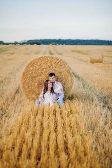 Giovani coppie felici su paglia, persone romantiche, bello paesaggio, stagione estiva