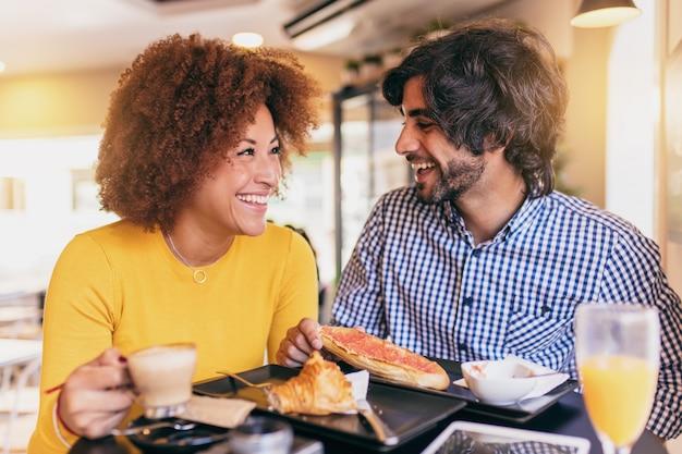 Giovani coppie fresche con una colazione al caffè. stanno bevendo succo d'arancia e mangiando a