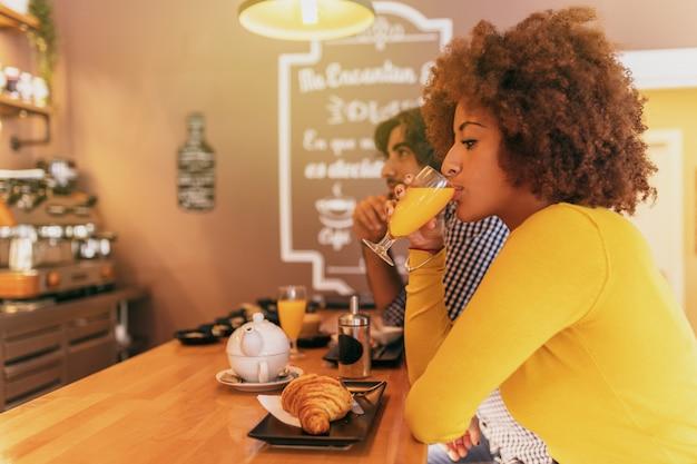 Giovani coppie fresche con una colazione, stanno bevendo tè e caffè in una panetteria