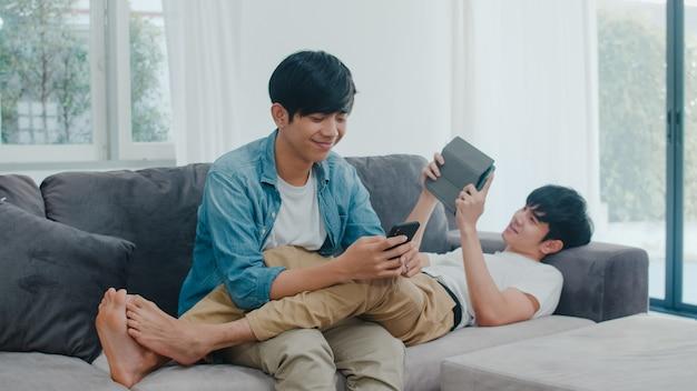 Giovani coppie gay del lgbtq facendo uso del telefono cellulare e della compressa a casa moderna. il maschio asiatico dell'amante felice si rilassa la risata e la tecnologia divertente giocano insieme in internet mentre si trovano il sofà in salone.