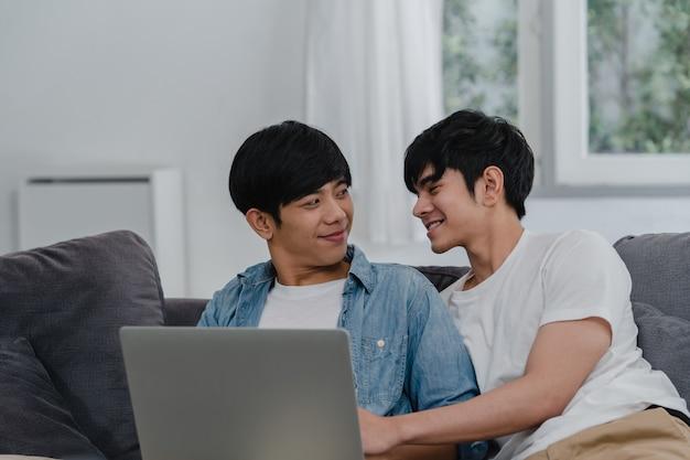 Giovani coppie gay facendo uso del computer portatile del computer a casa moderna. gli uomini asiatici lgbtq + si rilassano felici usando la tecnologia guardando film in internet insieme mentre giacciono sul divano nel salotto di casa.