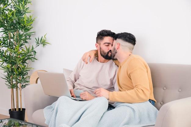 Giovani coppie gay romantiche che si siedono sul sofà che si bacia