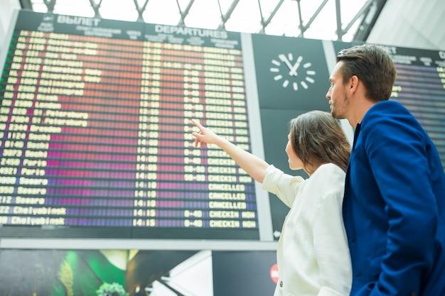 Giovani coppie in aeroporto internazionale che esamina il bordo di informazioni di volo